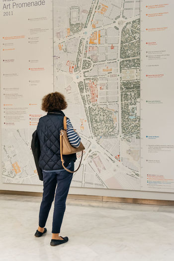 Woman looking at Madrid Map. Rear view Architecture Centro Cibeles Palace City Hall Madrid Madrid, Spain Map Rear View SPAIN Travel Woman Casual Clothing Centrocentrocibeles Culture Cultures Day Europe Exhibition Full Length Indoors  One Person Real People Spaın Tourism Visitor