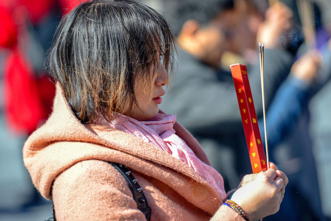 Worshippers hold incense sticks and pray at Yonghegong Lama Temple in Beijing, China. ASIA Beijing Lama Temple Monastery Smoke Worshippers Budhism Casual Clothing Child Childhood China Close-up Day Females Focus On Foreground Hairstyle Headshot History Holding Innocence Lama Leisure Activity Lifestyles Looking One Person Prayer Real People Religion Scarf Side View Stick Temple Warm Clothing Winter Women Yonghe Yonghegong
