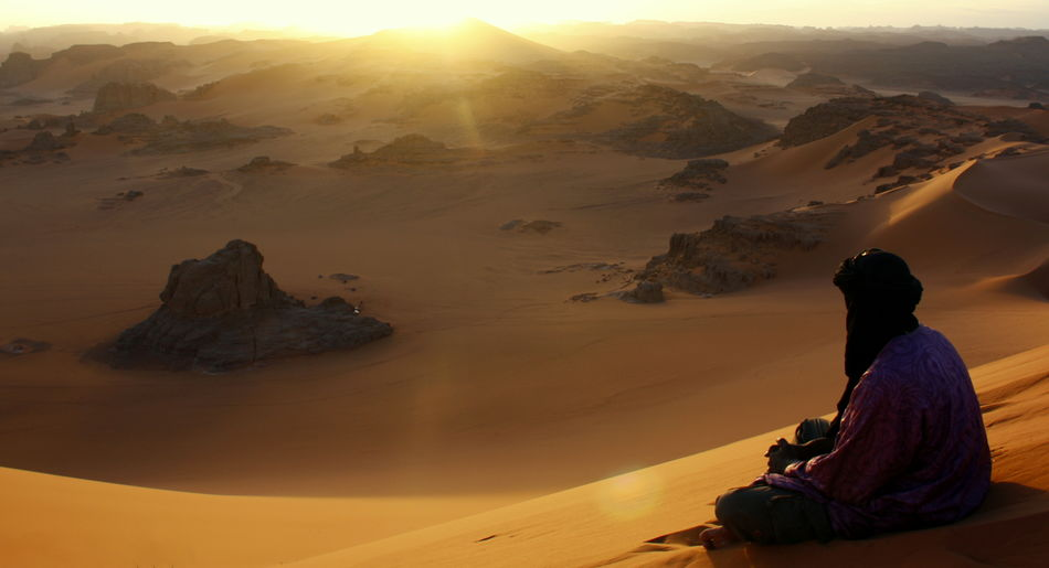 Rear View Of Man Sitting On Desert At Sunset