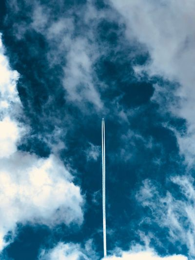 Low Angle View Of Vapor Trail Against Cloudy Sky