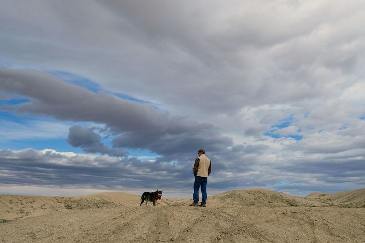 Rear view of man with dog standing at desert