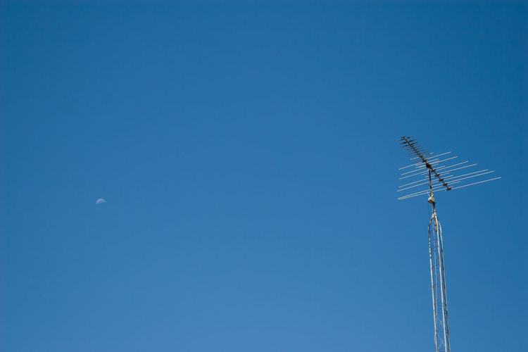 Low angle view of antenna against clear blue sky