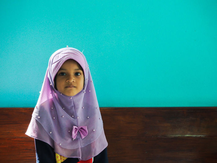 Portrait of girl wearing hijab against green wall