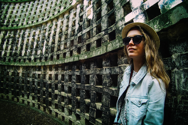 Young woman in sunglasses standing against patterned wall