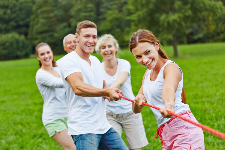 Smiling Family Pulling Rope On Field Against Trees