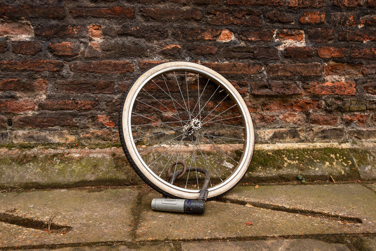 A lone bicycle wheel with tyre but missing its bike is securely locked with D lock against an old red brick wall. D Lock Missing Stolen Bicycle Brick Brick Wall Building Exterior Built Structure Circle Geometric Shape Land Vehicle Lock Metal Mode Of Transportation Old Outdoors Shape Spoke Stone Wall Tire Transportation Wall Wall - Building Feature Wheel