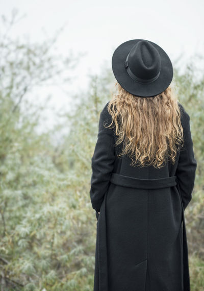Rear view of person wearing hat standing on field