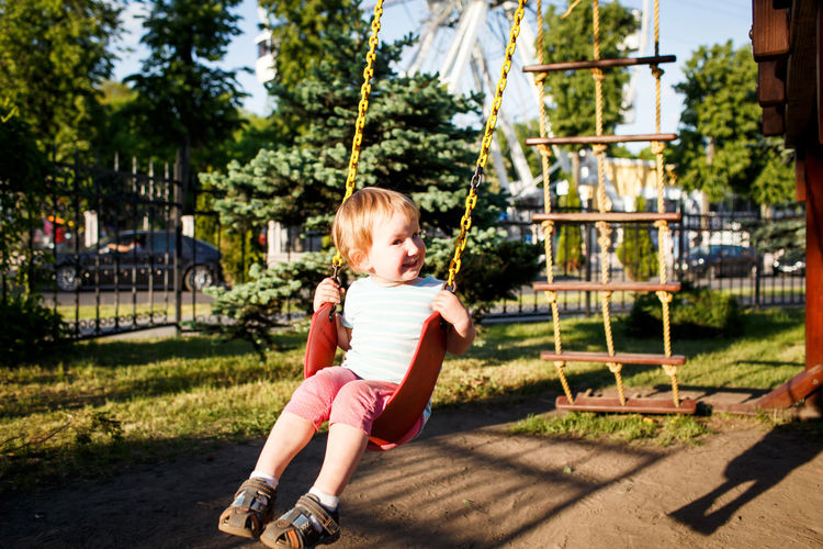 Full length portrait of girl on swing at park during sunny day