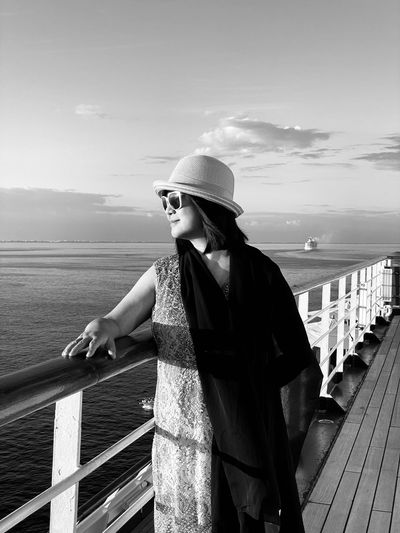Woman wearing sunglasses while standing by railing of boat in sea against sky