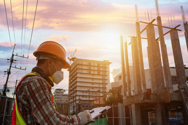 Man working at construction site against sky during sunset