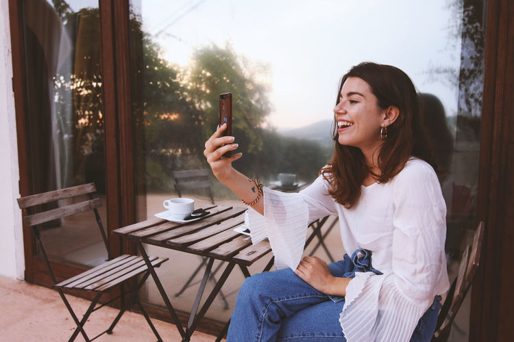 Young woman using mobile phone at home smiling