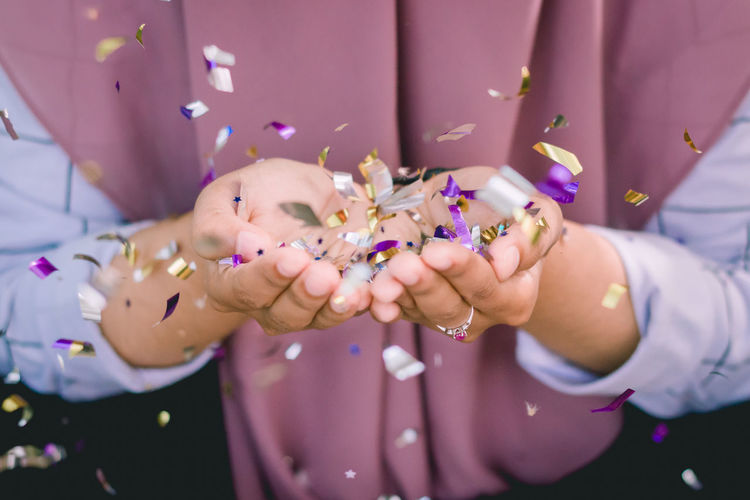 Midsection Of Woman Holding Confetti