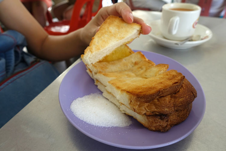 Close up female hand holding a slice of toasted butter sugar bread. Asian traditional breakfast. Asian Breakfast Bread Breakfast Butter Sugar Close-up Coffee Coffee - Drink Coffee Cup Crockery Cup Finger Focus On Foreground Food Food And Drink Freshness Hand Human Hand Indoors  One Person Plate Ready-to-eat Real People Snack Table Toasted Bread