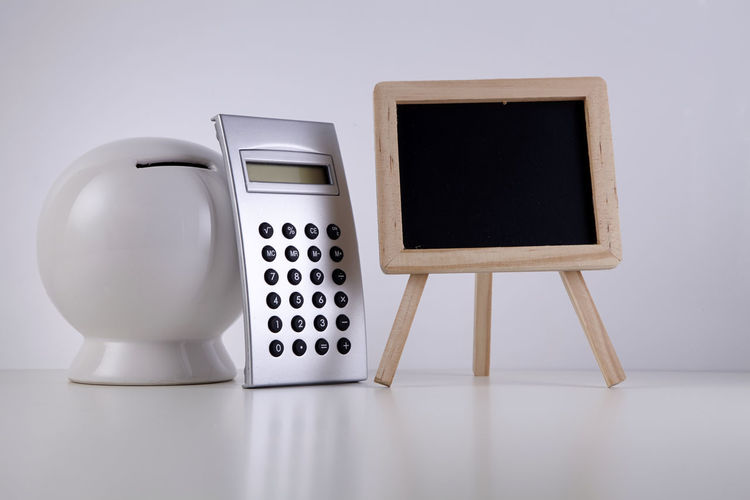Close-up of piggy bank and calculator with blackboard on table against white background