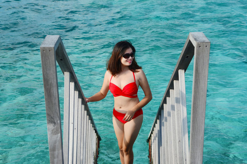 Portrait of beautiful woman standing on railing against sea