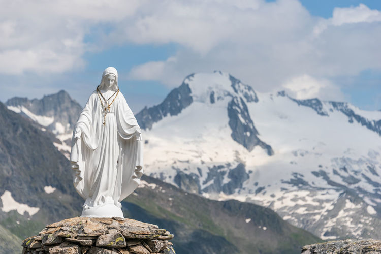 White statue of virgin mary, mother of god, placed on top of the mountain, blue sky, white clouds.