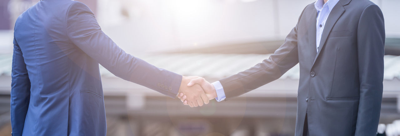 Midsection Of Businessmen Shaking Hands In City