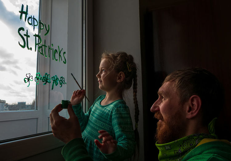 Girl writing on window with father at home