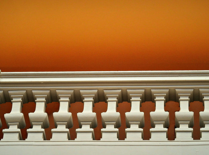 Low Angle View Of Railing Against Orange Background