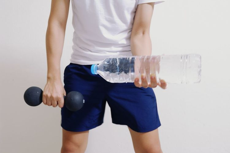 Exercise with a bottle of water. Exercising Human Hand Athlete Sport Gym White Background Exercising Healthy Lifestyle Men Strength Water Weight Training  Exercise Equipment Health Club Cross Training Exercise Class Weights Exercise Machine Human Muscle Weightlifting Strength Training Body Building