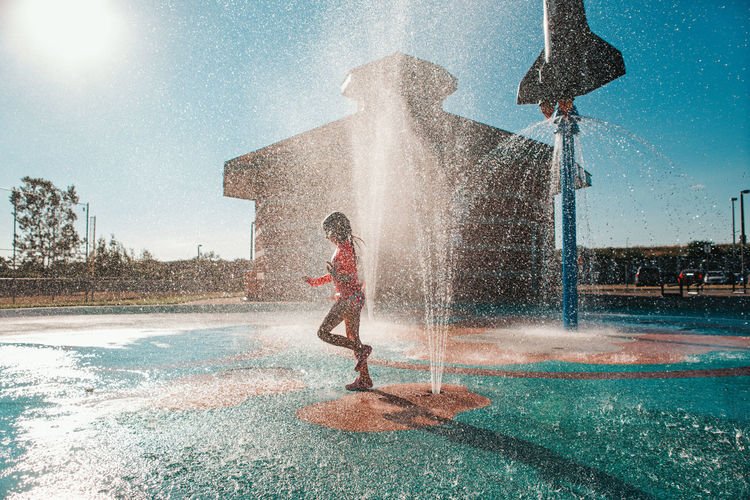 Cute adorable caucasian funny girl playing on splash pad playground on summer day. seasonal water s