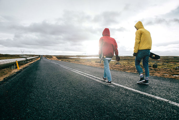 Full length of young man and woman skateboarding on road against landscape