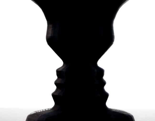 Close-up of silhouette statue against white background