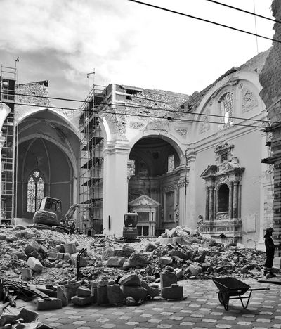 L'Aquila after the earthquake: church of Santa Maria di Collemaggio Abruzzo L'Aquila Rubble Wall Wheelbarrow Arches Architecture Black And White Blackandwhite Building Exterior Built Structure Clouds And Sky Digger Earthquake Earthquake In Italy Earthquake L'aquila Firefighters Italy Large Group Of People Place Of Worship Real People Religion Rubble Ruined Building Sky Spirituality
