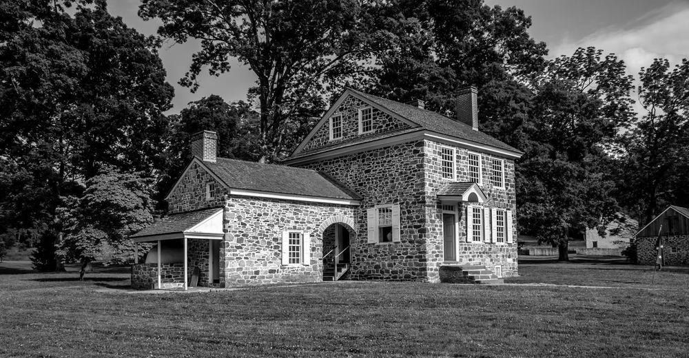 This is a photo of George Washington's Headquarters in Valley Forge National Park. While there are many building in Valley Forge National Historical Park that are original to the time of the encampment, none holds more historical significance than Washington's Headquarters. For most of the six-month encampment, Washington made his home in this stone building, meeting with advisers as they made plans, not only for the encampment, but the continuation of the war. Architecture Blackandwhite Built Structure Day Daytime Exterior EyeEm Best Shots EyeEm Gallery EyeEm Nature Lover Façade George Washington Grass Green Color Growth Nature No People Outdoors Revolutionary War Sky Sun Light Tranquility Tree Tree Valley Forge National Park Washingtons Headquarters