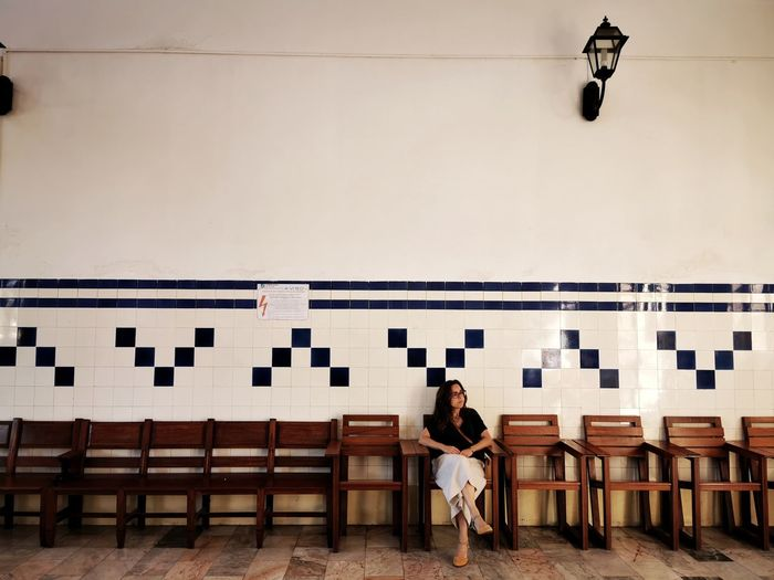 Woman sitting on bench against wall