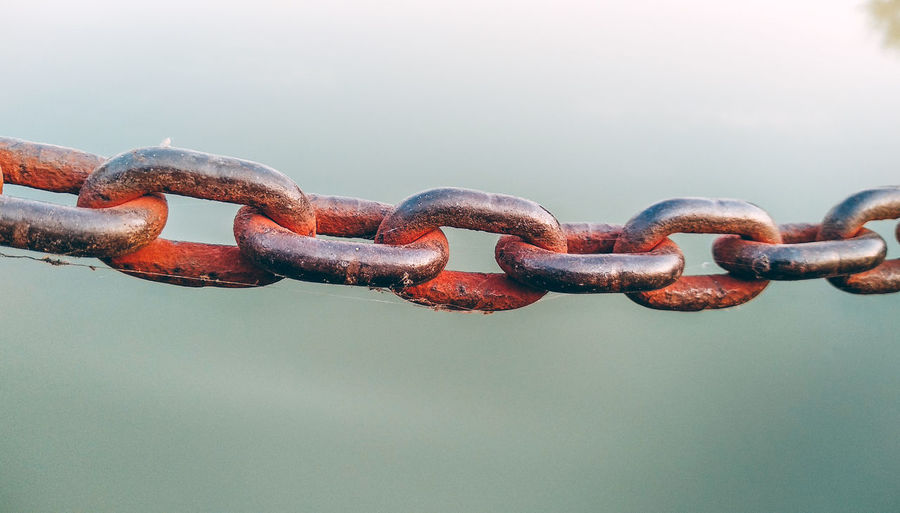 Close-up of rusty metal chain against fence