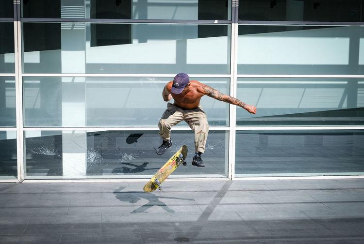 Full length of shirtless man jumping