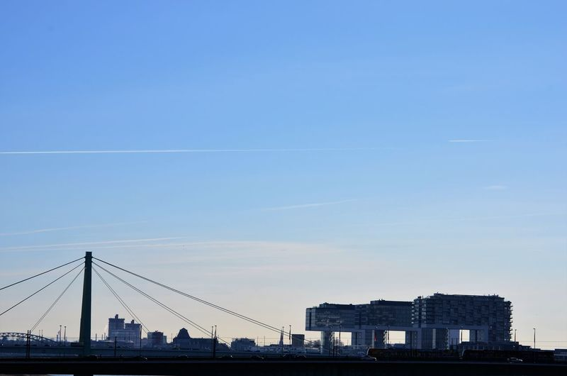 Suspension bridge and buildings against clear blue sky