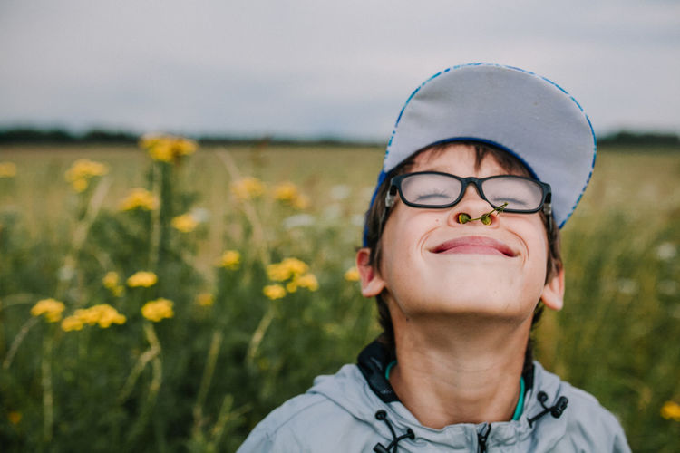 Smiling boy with buds in nose wearing eyeglasses