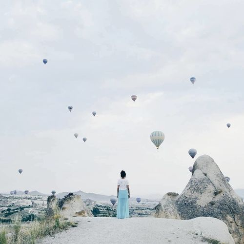 Rear view of woman standing against hot air balloons in sky at cappadocia