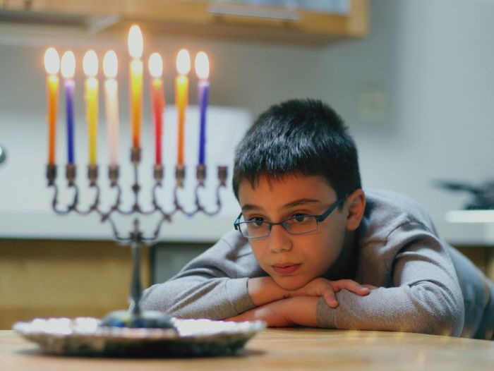 Boy looking at lit candles on hanukkah menorah