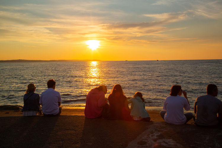 Baltic Sea Adult Beauty In Nature Group Of People Horizon Horizon Over Water Men Nature Orange Color Outdoors Positive Emotion Real People Rear View Scenics - Nature Sea Sitting Sky Sun Sunset Togetherness Water Women
