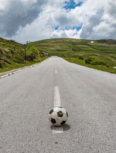 View of soccer ball on road against cloudy sky
