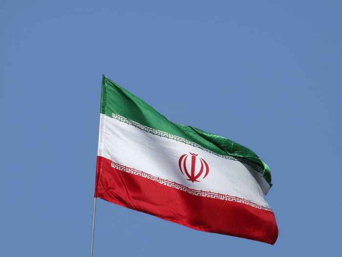 Low angle view of iranian flag against clear blue sky