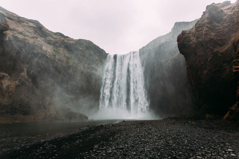 Low angle view of waterfall against clear sky