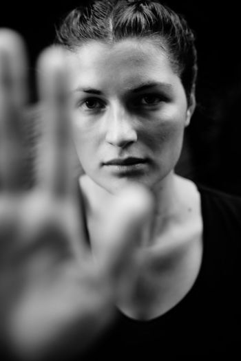 Portrait of serious young woman showing stop gesture against black background