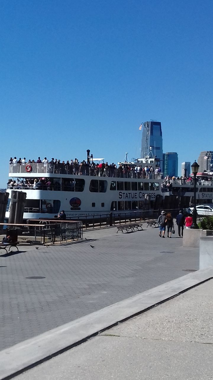 clear sky, built structure, real people, architecture, transportation, day, men, building exterior, outdoors, mode of transport, nautical vessel, harbor, large group of people, lifestyles, city, women, sky, water, nature, cityscape, people