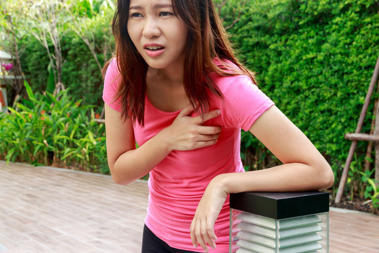 Woman suffering from chest pain while standing at park