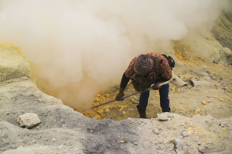 Miner Digging Sulfur At Volcanic Crater