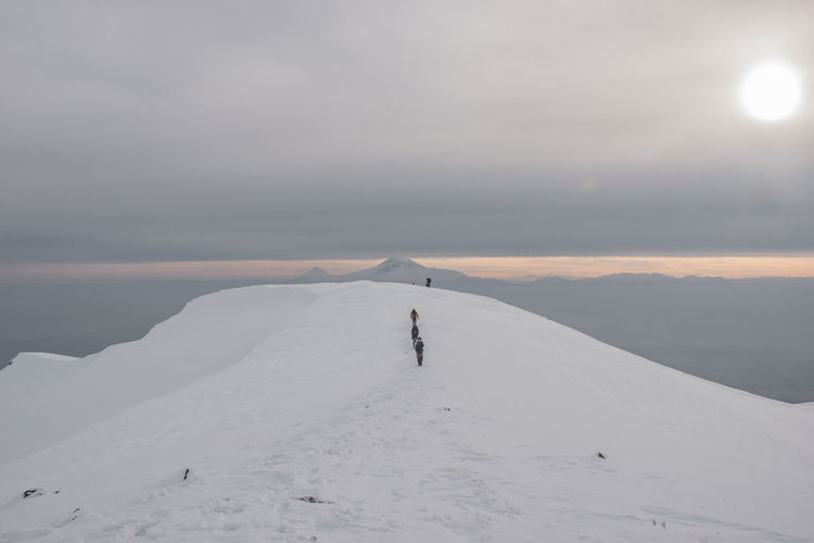 People on snowcapped mountain against sky during sunset