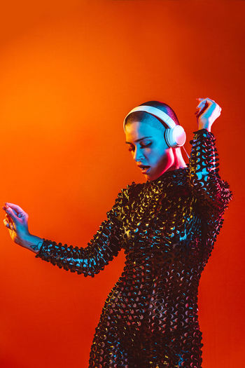 Young woman with shaved head wearing headphones against orange background