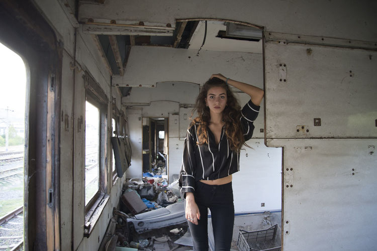 Portrait Of Young Woman Standing In Abandoned Train