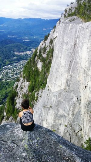 Rear View Of Woman Looking At View While Sitting On Cliff