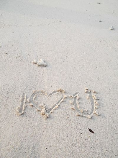 High angle view of heart shape with i love you text on beach