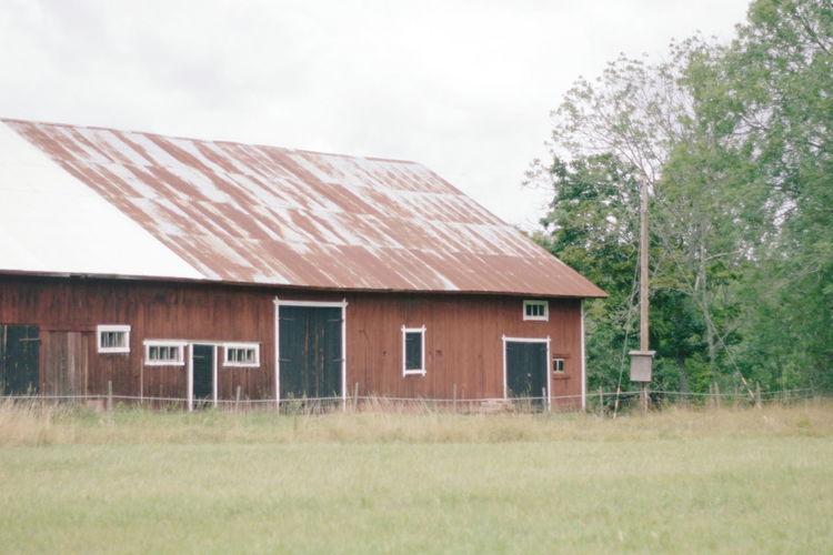 House on grassy field against sky